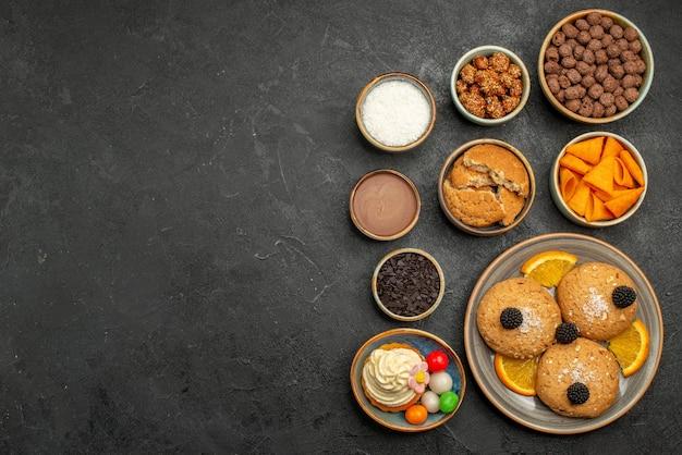 Widok z góry słodkie ciasteczka z frytkami i plastrami pomarańczy na ciemnej powierzchni ciasteczko fruti ciastko słodkie ciasto