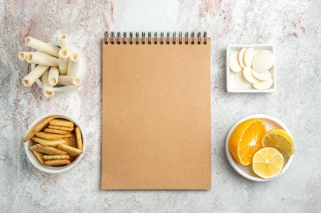 Widok z góry słodkie ciasteczka z krakersami i notatnik na białych owocach ciasteczek cukierków stołowych