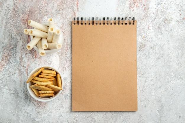 Widok z góry słodkie ciasteczka z krakersami i notatnik na białym stole z owocami ciasteczka cukierki