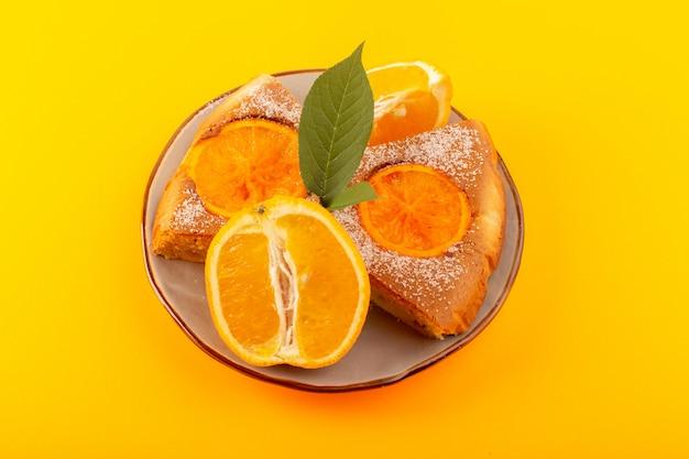 Widok z góry słodkie ciasto pomarańczowe słodkie pyszne kromki ciasta wraz z plasterkami pomarańczy wewnątrz okrągłego talerza na żółtym tle biszkopt słodki cukier
