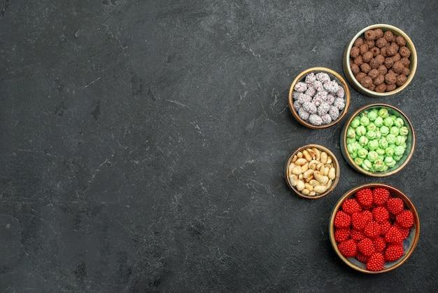 Widok z góry słodkie cukierki wewnątrz małych doniczek na szarym tle cukierki słodka herbata z cukrem