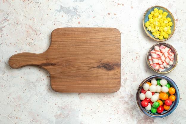 Widok z góry słodkie cukierki z konfiturami na białym stole tęczowy kolor cukierków