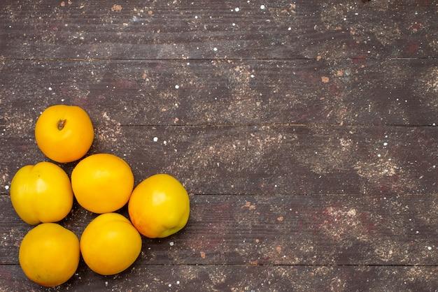 Widok z góry słodkie łagodne morele pomarańczowe kolorowe pyszne letnie owoce na ciemnym tle ciasto owocowe świeże zdjęcie