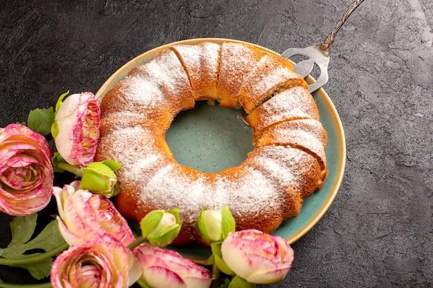 Widok z góry słodkie okrągłe ciasto z cukrem pudrem na wierzchu w plasterkach słodkie pyszne izolowane wewnątrz talerza wraz z kwiatami i szarym ciasteczkowym ciasteczkiem cukrowym