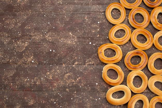 Widok z góry słodkie okrągłe krakersy suszone i smaczne przekąski na brązowym, ciasteczkowym mleku do picia