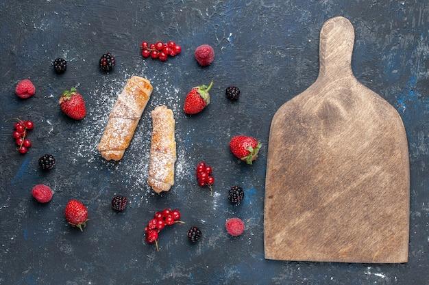 Widok z góry słodkie pyszne bransoletki z nadzieniem pyszne pieczone z owocami i jagodami na ciemnym biurku piec ciasto deserowe