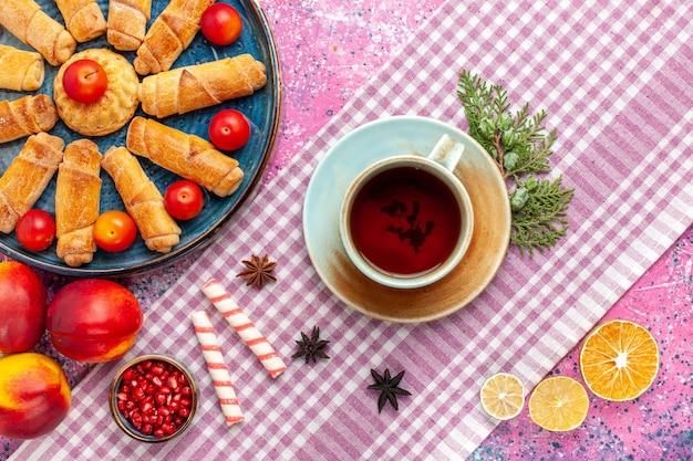 Widok z góry słodkie pyszne bułeczki w tacy ze śliwkami, świeżymi brzoskwiniami i filiżanką herbaty na jasnoróżowym biurku