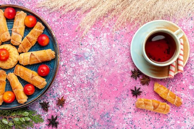 Widok z góry słodkie pyszne bułeczki w tacy ze świeżymi kwaśnymi śliwkami i filiżanką herbaty na jasnoróżowym biurku