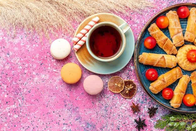 Widok z góry słodkie pyszne bułeczki w tacy ze świeżymi śliwkami francuskimi makaronikami i filiżanką herbaty na jasnoróżowym biurku
