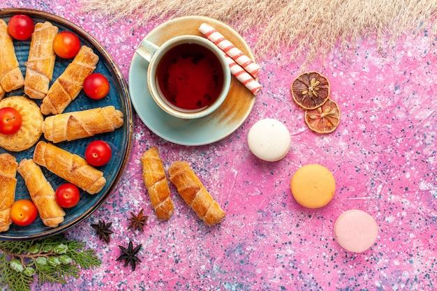 Widok z góry słodkie pyszne bułeczki w tacy ze świeżymi śliwkami makaronikami i filiżanką herbaty na jasnoróżowym biurku