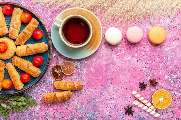 Widok z góry słodkie pyszne bułeczki ze świeżymi śliwkami francuskimi makaronikami i filiżanką herbaty na jasnoróżowym biurku