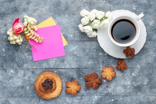 Widok z góry słodkie pyszne ciasteczka z filiżanką kawy na szarym tle ciasteczka ciasteczka słodkie