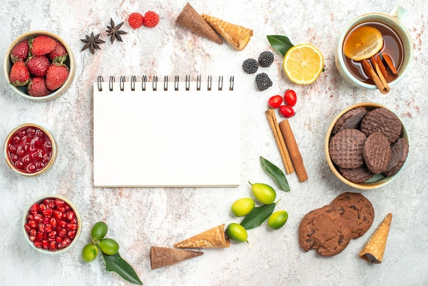 Widok z góry słodycze biały notatnik filiżanka herbaty ciasteczka dżem laski cynamonu granat jagody cytryna