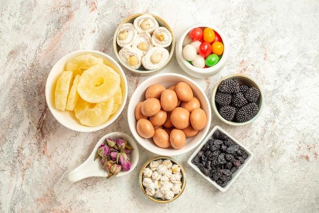 Widok z góry słodycze na stole apetyczne słodycze w miseczkach na środku białego stołu