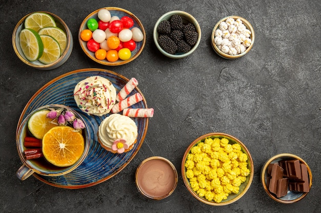 Widok z góry słodycze na stole miski jagód czekolada owoce cytrusowe kolorowe słodycze oraz talerz babeczek i filiżanka herbaty ziołowej z cynamonem na ciemnym stole