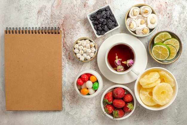 Widok z góry słodycze w miseczkach plasterki limonek suszony ananas i słodycze obok kremowego notatnika i filiżanki czarnej herbaty po prawej stronie stołu