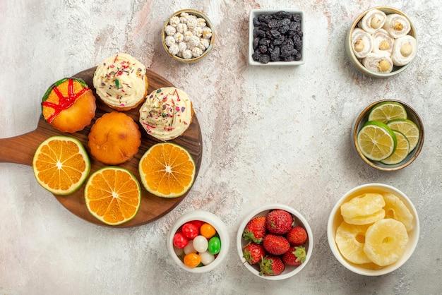 Widok z góry słodycze w miskach drewniana deska z ciasteczkami i pomarańczą obok cytryny truskawki suszony ananas i turecka rozkosz w miskach na stole