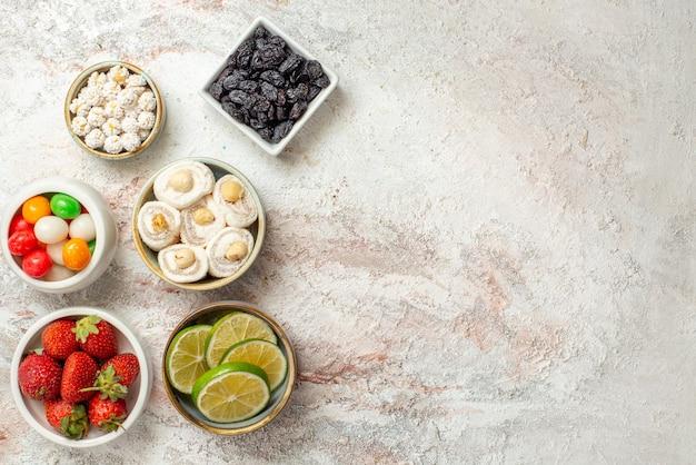 Widok z góry słodycze w miskach miski apetycznych jagód suszone ananasy i inne słodycze na białym stole