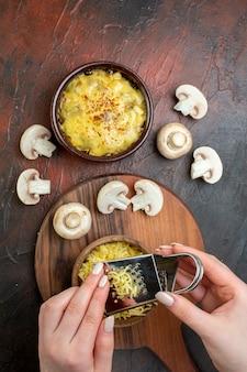 Widok z góry smaczna julienne w misce surowe grzyby kobieta ręce tarcie mosarelli na brązowym stole