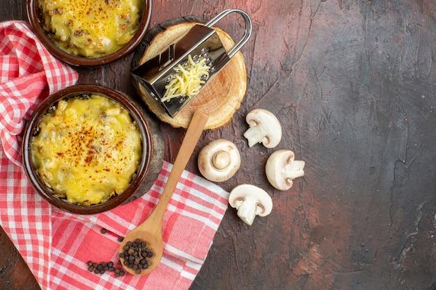 Widok z góry smaczna julienne w miskach grzyby miska na mleko tarka na desce drewniana łyżka na ciemnoczerwonym stole