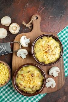 Widok z góry smaczna julienne w miskach na drewnianej misce z deską do serwowania z tartą tarką do mosarelli na brązowym stole