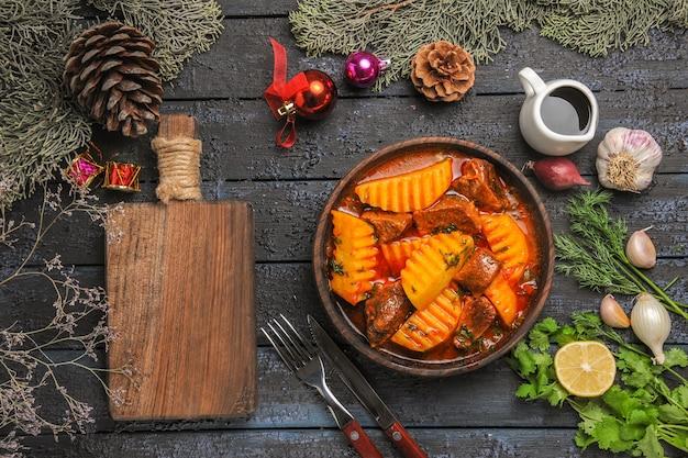 Widok z góry smaczna mięsna zupa z zieleniną i ziemniakami na ciemnym biurku