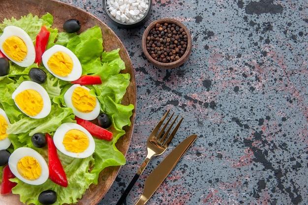 Widok z góry smaczna sałatka jajeczna z zieloną sałatą i oliwkami na jasnym tle