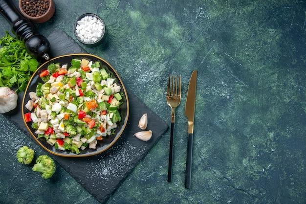 Widok z góry smaczna sałatka jarzynowa wewnątrz płyty na ciemnoniebieskim tle kolor kuchnia obiad restauracja jedzenie dieta posiłek