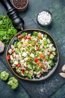 Widok z góry smaczna sałatka jarzynowa wewnątrz płyty na ciemnoniebieskim tle kolor kuchnia obiad restauracja zdrowa dieta posiłek