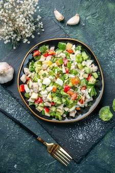 Widok z góry smaczna sałatka jarzynowa wewnątrz płyty na ciemnoniebieskim tle kolor kuchnia obiad zdrowa żywność dieta posiłek