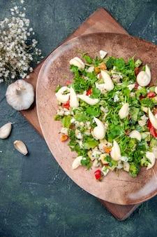 Widok z góry smaczna sałatka jarzynowa wewnątrz płyty na ciemnoniebieskim tle kuchnia restauracja obiad posiłek obiad zdrowie fit kuchnia kolor