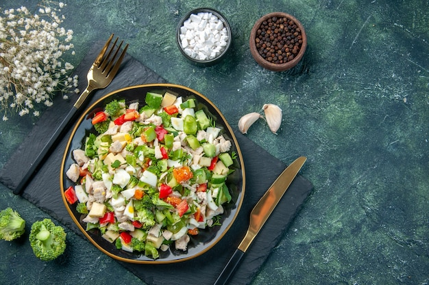 Widok z góry smaczna sałatka jarzynowa wewnątrz płyty na ciemnoniebieskim tle kuchnia restauracja świeży posiłek kolor zdrowy obiad dieta