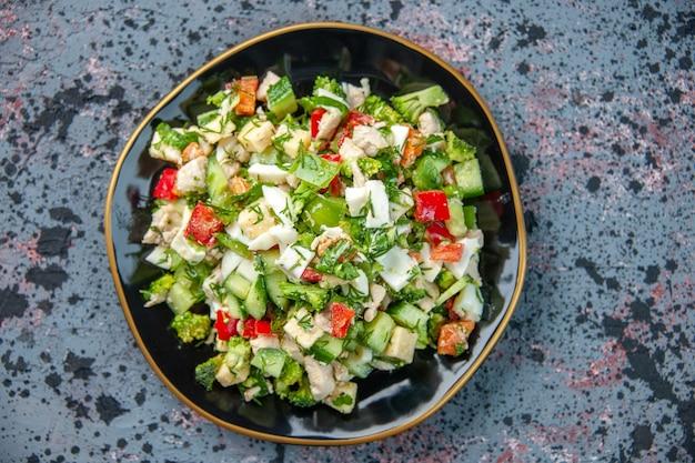 Widok z góry smaczna sałatka jarzynowa wewnątrz płyty na ciemnym tle kuchnia obiad restauracja świeży posiłek dieta zdrowotna kolor
