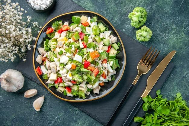 Widok z góry smaczna sałatka jarzynowa wewnątrz płyty z widelcem na ciemnoniebieskim tle posiłek w restauracji kolor prozdrowotna dieta świeża kuchnia obiadowa