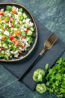 Widok z góry smaczna sałatka jarzynowa wewnątrz talerza z widelcem na ciemnym tle posiłek w restauracji kolor zdrowie dieta świeża kuchnia obiad