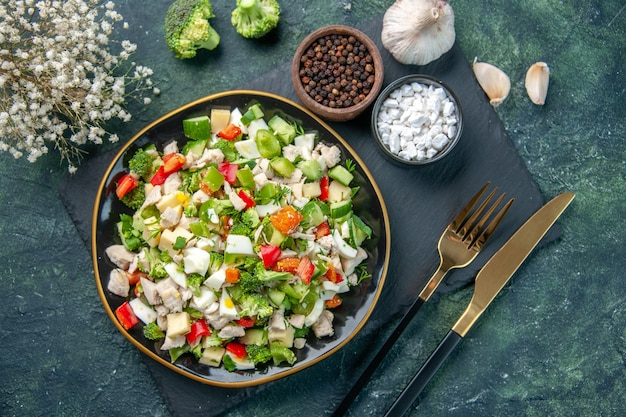 Widok z góry smaczna sałatka jarzynowa wewnątrz talerza ze sztućcami na ciemnoniebieskim tle kuchnia restauracja świeży posiłek zdrowie obiad dieta kolor