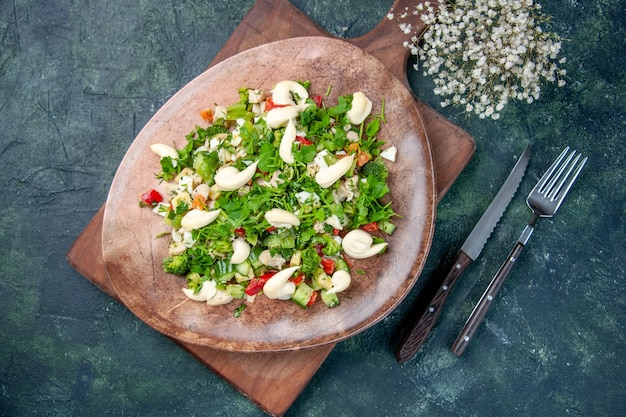Widok z góry smaczna sałatka jarzynowa wewnątrz talerza ze sztućcami na ciemnoniebieskim tle kuchnia zdrowie kolor pasuje obiad kuchnia dieta obiad posiłek restauracja