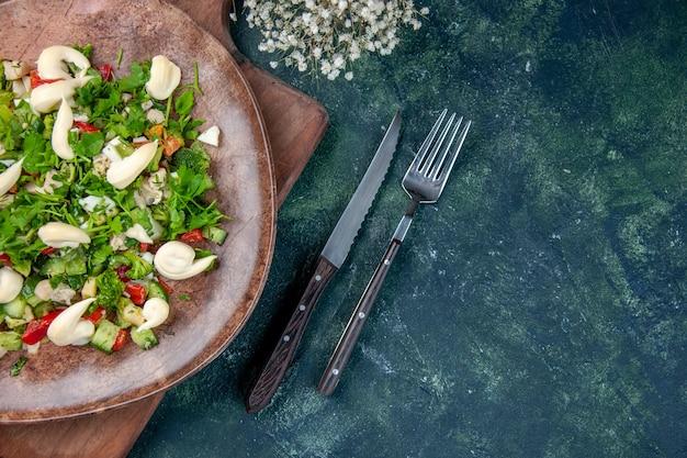 Widok z góry smaczna sałatka jarzynowa wewnątrz talerza ze sztućcami na ciemnoniebieskim tle kuchnia zdrowie kolor pasuje obiad kuchnia dieta obiad restauracja