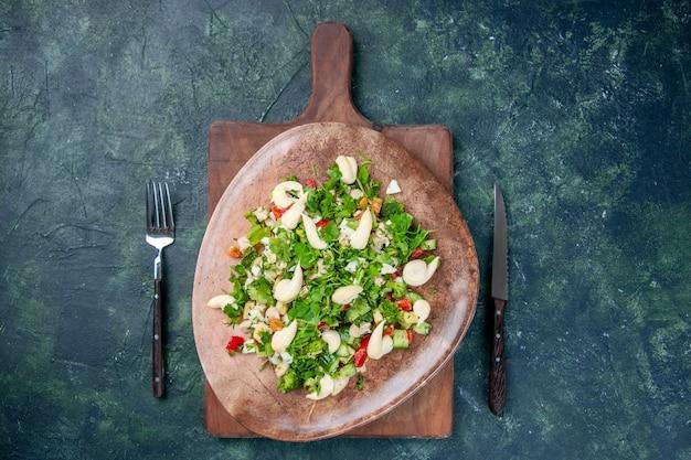 Widok z góry smaczna sałatka jarzynowa wewnątrz talerza ze sztućcami na ciemnoniebieskim tle kuchnia zdrowie kolor pasuje restauracja obiad kuchnia obiad posiłek