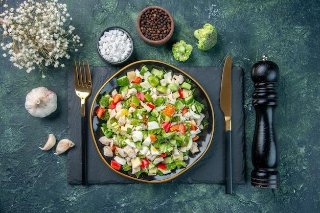 Widok z góry smaczna sałatka jarzynowa wewnątrz talerza ze sztućcami na ciemnym tle kuchnia restauracja świeży posiłek kolor zdrowy obiad dieta