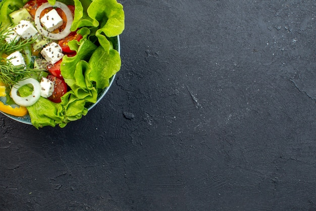 Widok z góry smaczna sałatka jarzynowa z serem, ogórkami i pomidorami na ciemnym tle