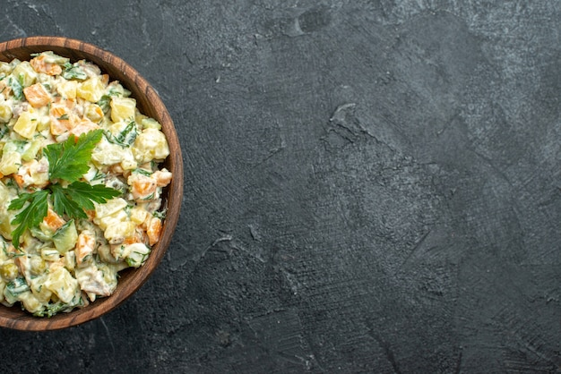 Widok z góry smaczna sałatka majonezowa wewnątrz brązowego talerza na czarno