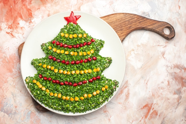 Widok z góry smaczna sałatka wakacyjna w kształcie drzewa nowego roku na jasnym tle