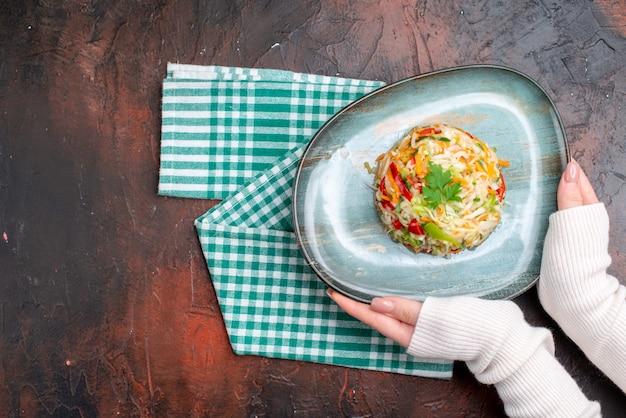 Widok z góry smaczna sałatka warzywna wewnątrz talerza z kobiecymi rękami na ciemnym stole