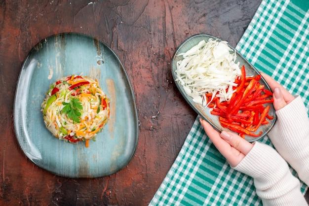 Widok z góry smaczna sałatka warzywna wewnątrz talerza z pokrojoną kapustą i papryką na ciemnym stole