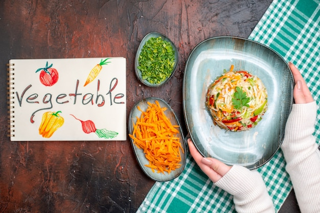 Widok z góry smaczna sałatka warzywna wewnątrz talerza z zieleniną i pokrojoną marchewką na ciemnym stole