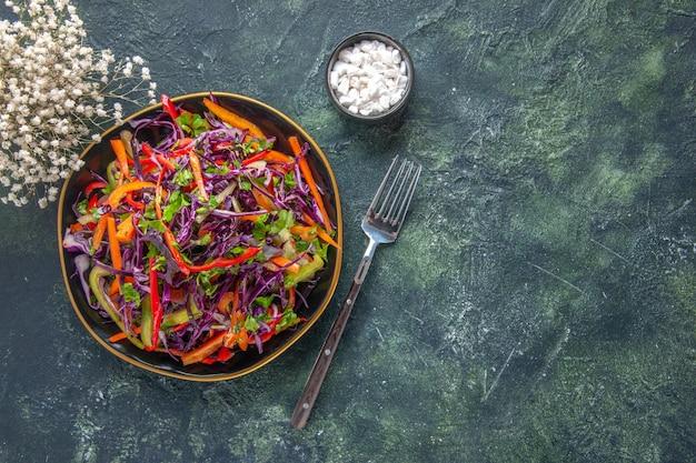 Widok z góry smaczna sałatka z kapusty z papryką wewnątrz płyty na ciemnym tle zdrowy chleb przekąska posiłek dieta obiad świąteczne jedzenie