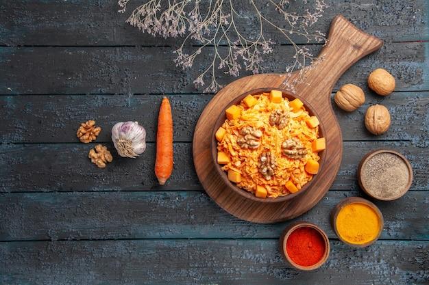 Widok z góry smaczna sałatka z marchwi z orzechami włoskimi i przyprawami na ciemnoniebieskim biurku sałatka z orzechów zdrowa dieta kolorowa żywność