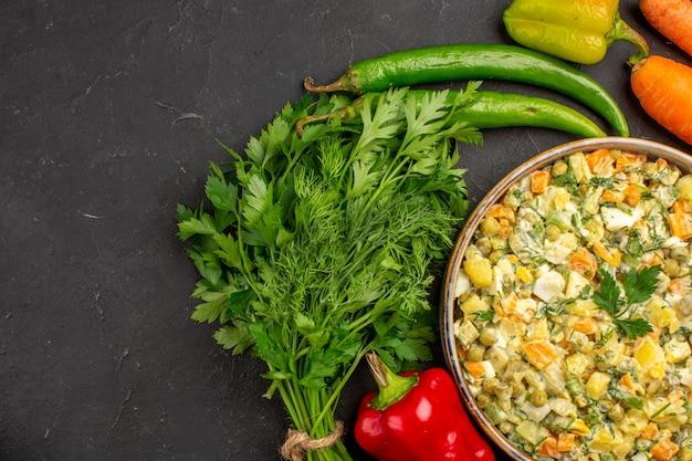 Widok z góry smaczna sałatka z zieleniną i warzywami na ciemnym tle