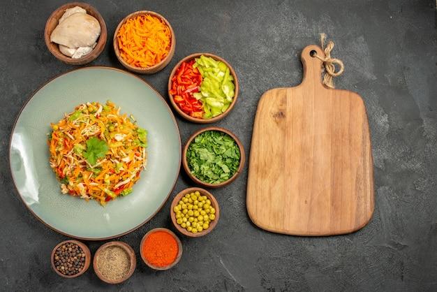 Widok z góry smaczna sałatka ze składnikami na diecie zdrowej żywności w kolorze szarym